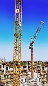 pic of construction crane  - a large lifting crane at the building site near a building under construction - JPG