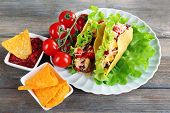 foto of nachos  - Tasty taco with nachos chips and tomato dip on plate on table close up - JPG