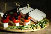 picture of canapes  - Cheese canapes with cherry tomatoes and olives on wooden tray close up - JPG