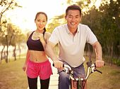 stock photo of exercise bike  - young asian couple running riding bike outdoors in park at sunset - JPG