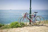 stock photo of lockups  - Two bicycles tied to a street pole with a view of the open sea in Rovinj Croatia - JPG