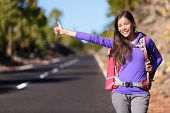 pic of thumb  - Travel hitchhiker woman backpacking hitchhiking thumbing happy walking on road side during holiday travel - JPG