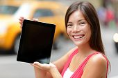 stock photo of cabs  - Tablet computer casual woman showing blank empty screen of tablet pc in New York City - JPG