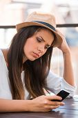 image of funky  - Depressed young woman in funky hat looking at mobile phone while sitting outdoors - JPG
