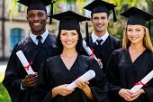 image of graduation gown  - Four college graduates in graduation gowns standing close to each other and smiling - JPG