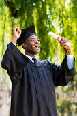 foto of graduation gown  - Happy young African man in graduation gowns holding diploma and rising arms up - JPG