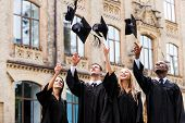 stock photo of graduation gown  - Four happy college graduates in graduation gowns throwing their mortar boards and smiling while standing near university - JPG