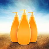 picture of suntanning  - Suntan Lotion Botlles in Sand on Sunny Seaside Beach as Blank Copy Space for text or graphics - JPG