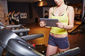 foto of sportive  - Fit girl in activewear using touchpad while training on sportive equipment - JPG