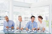 foto of concentration  - Concentrated business team sitting with their vote on the desk in the office - JPG