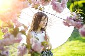 image of japan girl  - Cute little brunette girl looking forward with japanese parasol in pink cherry blossom in daylight in the garden copyspace horizontal picture - JPG