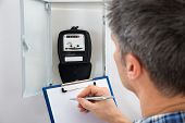 foto of electricity meter  - Technician Writing Reading Of Meter On Clipboard - JPG