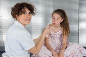 foto of auscultation  - Auscultation young girl doctor tries to clean her nose - JPG