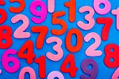 stock photo of zero  - A viariety of single digit numbers from one to nine including zero are mixed all over a blue background - JPG