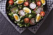 stock photo of sorrel  - Delicious salad with eggs radishes and sorrel close up on the table - JPG