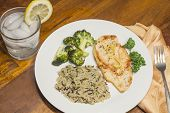 stock photo of crispy rice  - Crispy tender lemon chicken garnished with lemon twist with sides of herb wild rice and lemon broccoli - JPG