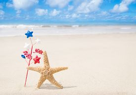 stock photo of starfish  - Patriotic USA background with starfishes and decorations on the sandy beach - JPG