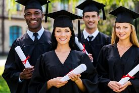 stock photo of graduation gown  - Four college graduates in graduation gowns standing close to each other and smiling - JPG