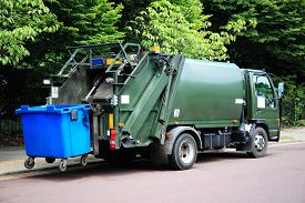 stock photo of dustbin  - Green garbage truck with an elevated blue wheelie bin at the rears - JPG