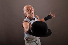 stock photo of hobo  - Old cheerful hobo posing with outworn black hat studio shot against gray background - JPG