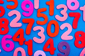 pic of number 7  - A viariety of single digit numbers from one to nine including zero are mixed all over a blue background - JPG