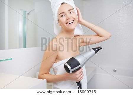The girl in the bathroom with hairdryer in hand