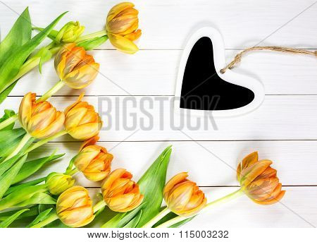 Yellow Tulips And Heart On White Wooden Table. Top View.
