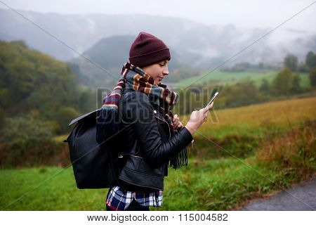 Woman hiker checks weather forecast via cell telephone while climbs the mountain