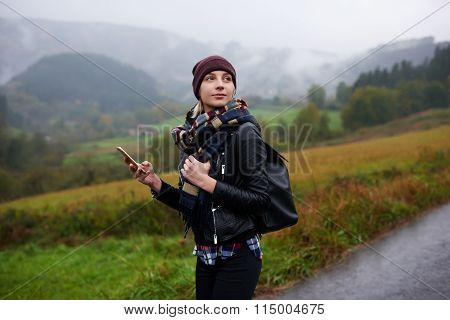 Trendy woman catches signal on her mobile phone while searching interesting places in mountains