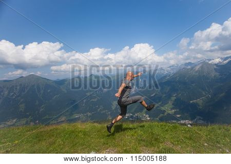 Man Jumping Off A Cliff In The Mountains In Summer