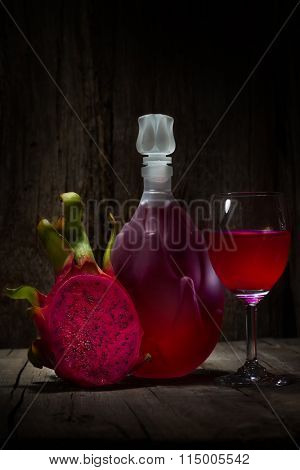 Full red Dragon Fruit wine glass goblet and bottle on wooden background
