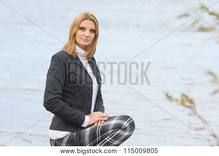 Young Beautiful Girl Sat Down By The River In The Warm Autumn Weather