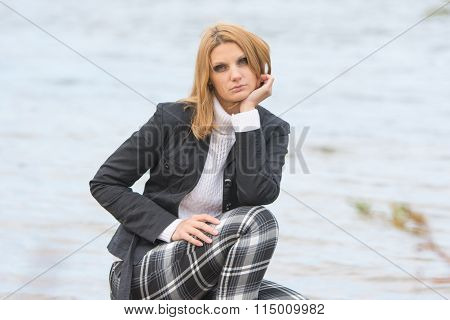 Beautiful Sad Girl Sat By The River In The Warm Autumn Weather
