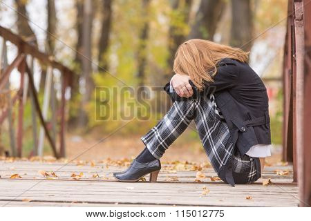 Sad Girl Sitting On A Bridge With Her Head Resting On His Knees