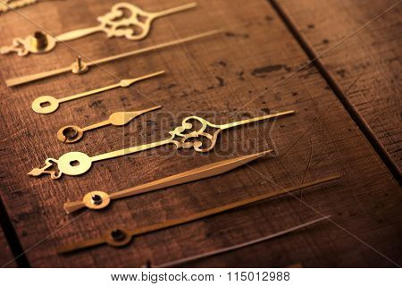 Clock hands or needle on old wooden surface. Time concept image.