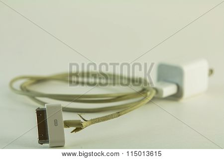 Torn white power cord for cellphone