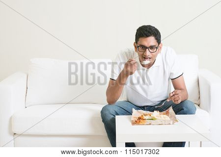 Young single Indian man eating food alone. Having nasi lemak as lunch. Lifestyle of Asian guy at home.