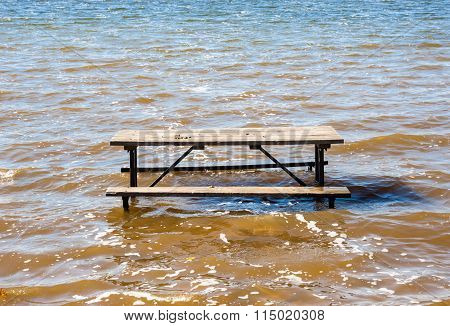 Empty Picnic Table In Muddy Brown Water