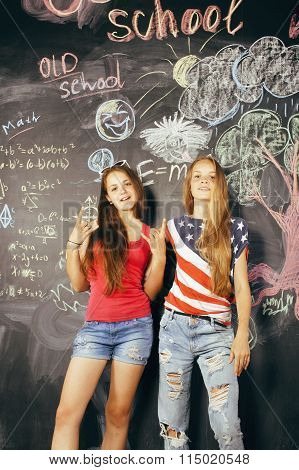 back to school after summer vacations, two teen girls in classroom with blackboard painted