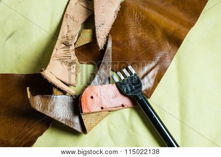 Leather Sewing Tools On A Real Leather Background.