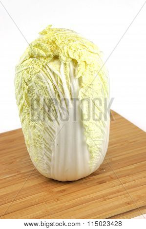 single Chinese cabbage on chopping board, vertical composition