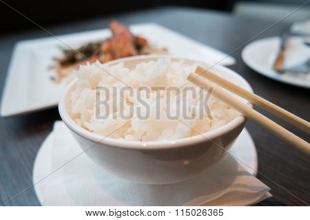 Plain rice in a bowl with chopsticks on it