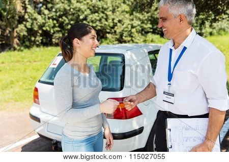 cheerful young woman being handed drivers license by senior driving instructor