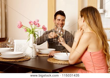 Young couple clinking glasses at home while having dinner, smiling.