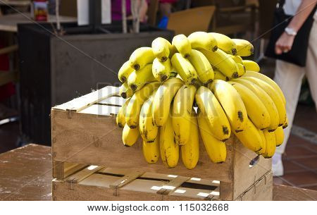Cluster Of Yellow Bananas On Wooden Box In The Street