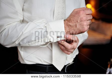 Groom Wears Cufflinks For Shirt