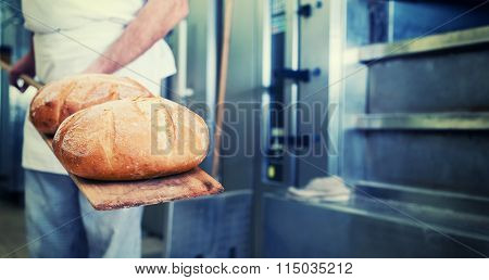 Baker in bakery with bread on shovel standing in front of oven, filtered image