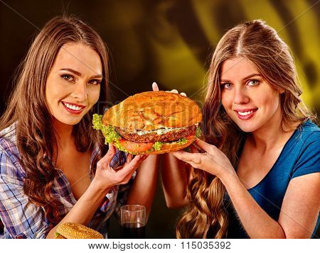 Two girls holding burger with two sides. Fastfood concept.