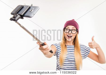 Happy Girl In Cap And Glasses Making Photo By Selfie Stick And Thumbs Up