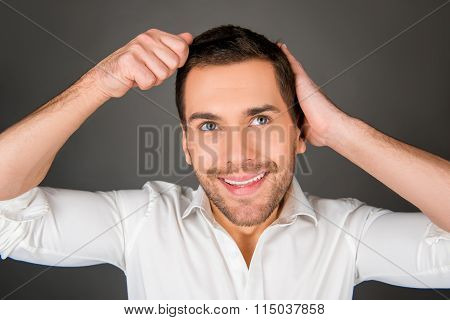 Handsome Cheerful Young Man Combing His Hair